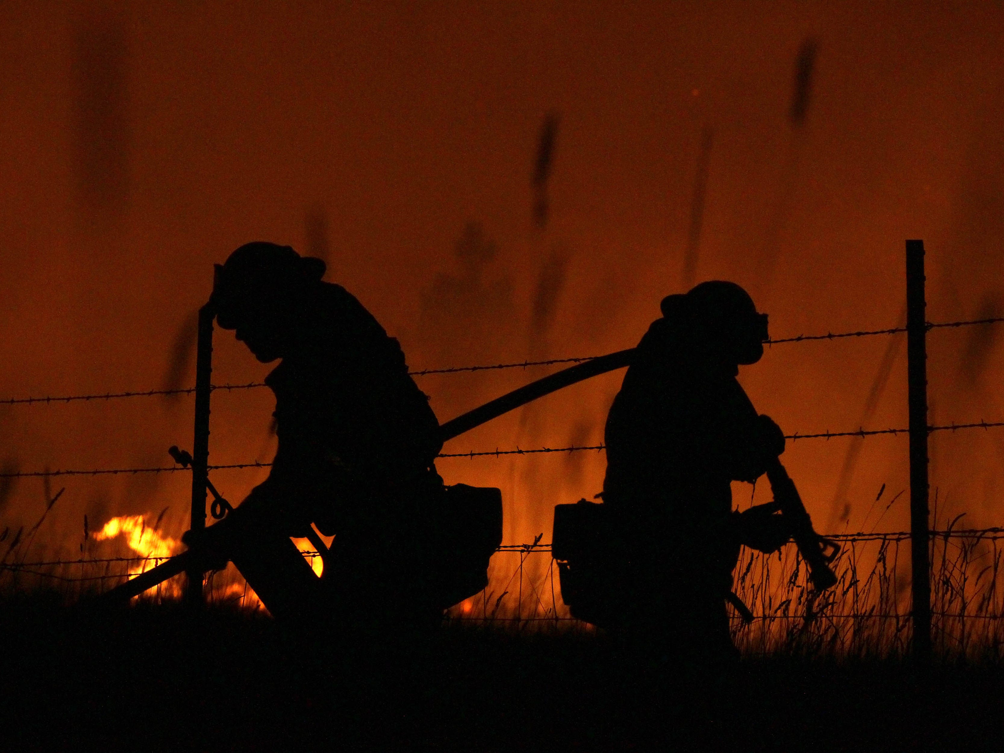Firefighters keep standing guard along I-5 north of the Pollard Flat exit as the Delta Fire flares up in the background on Friday evening, Sept. 7, 2018. (Hung T. Vu/Special to the Record Searchlight)