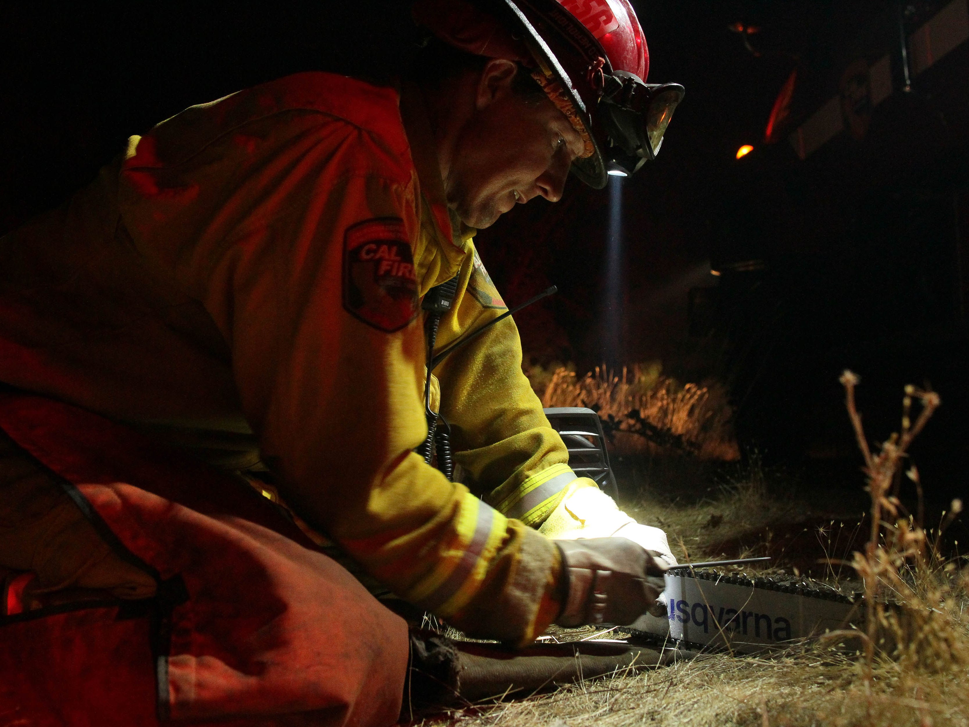 While on a break, firefighter Todd Wallace sharpens a chainsaw after putting out flareups  from the Delta Fire along I-5 north of the Pollard Flat exit on Friday night, Seot. 7, 2018. (Hung T. Vu/ Special to the Record Searchlight)
