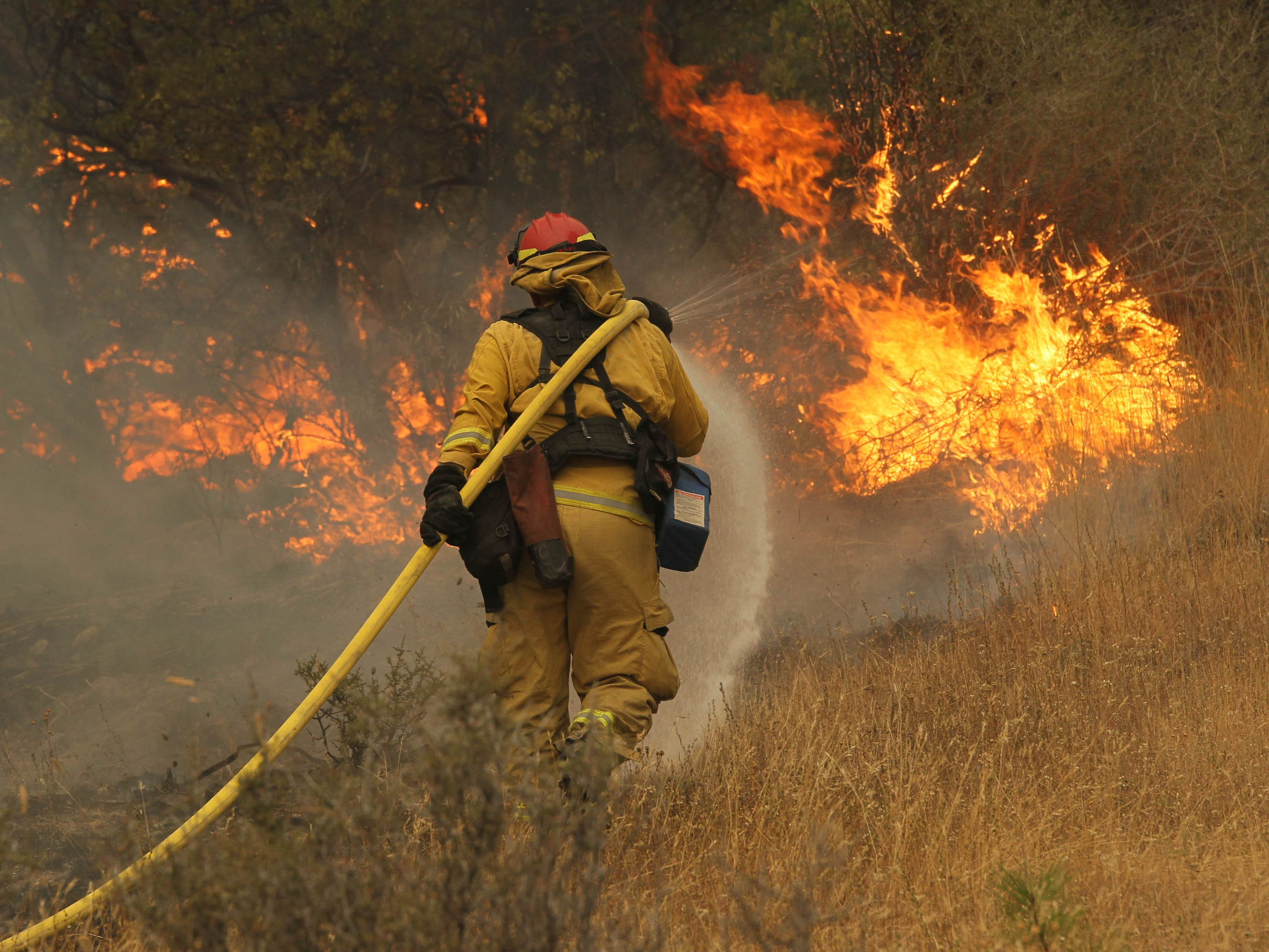 Fire Capt. Norm Alexander of Yocha Dehe Fire in Yolo County puts some water on the flames of the Delta Fire as it burns by the I-5 Earl Sholes Memorial Bridge on Friday, Sept. 7, 2018. (Hung T. Vu/Special to the Record Searchlight)