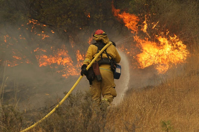 Fire Capt. Norm Alexander of Yocha Dehe Fire in Yolo County is shown putting water on the flames of the Delta Fire as it burned Friday, Sept. 7, 2015, by the I-5 Earl Sholes Memorial Bridge. (Hung T. Vu/Special to the Record Searchlight)
