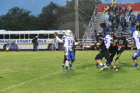 Reagan County quarterback Justin Chavez throws the ball in the rain while being pressured by Ballinger's Cooper Bean during their game Friday, Sept. 7, 2018, at Bearcat Stadium in Ballinger.