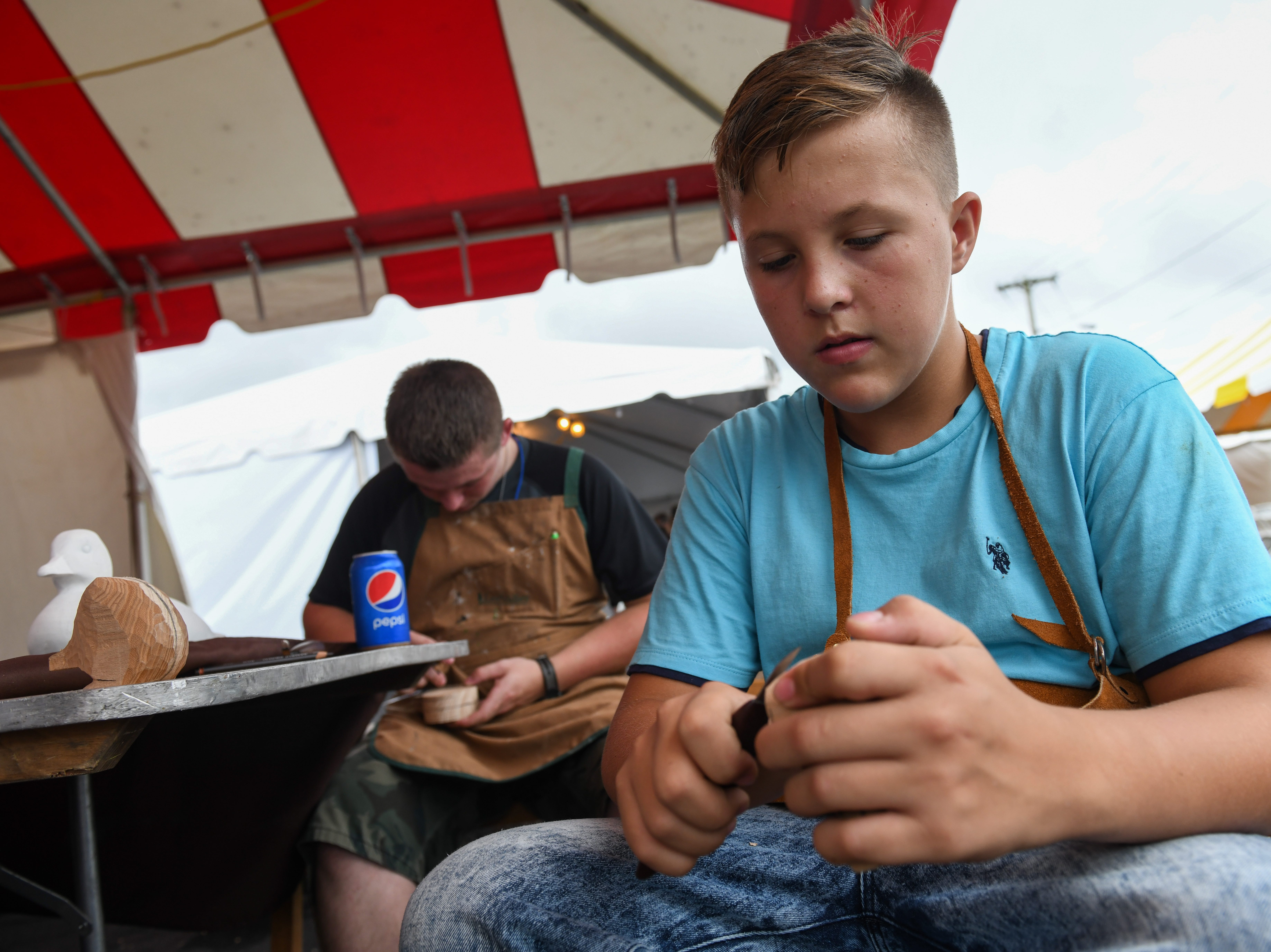 Apprentice Wyatt Lowe carves at the National Folk Festival in Salisbury on Saturday, Sept. 8.
