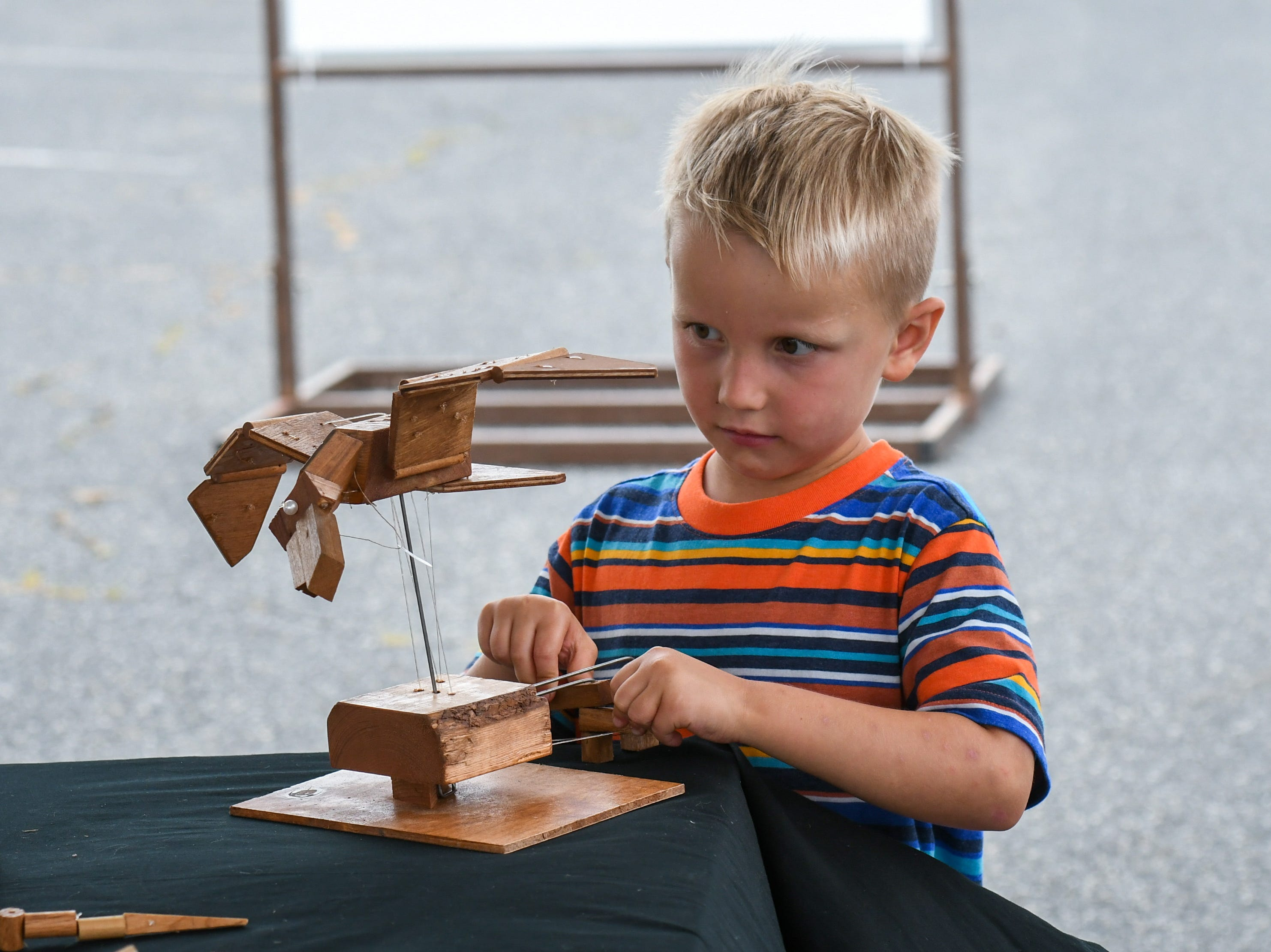 4-year-old Alexander Pope checks out one of the Jeghetto group's puppets at the National Folk Festival in Salisbury on Saturday, Sept. 8.