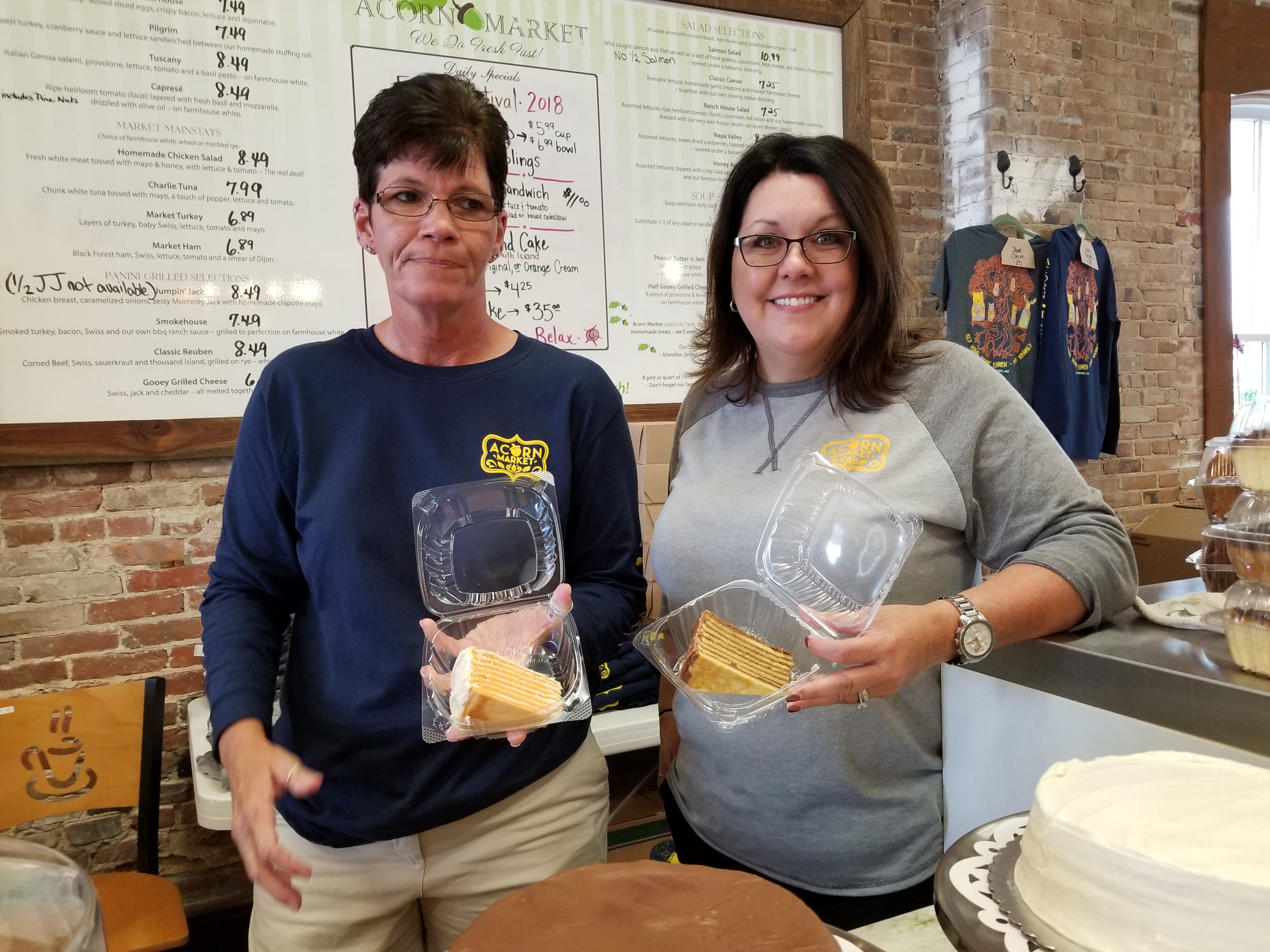 Tina Lee (left) and Christine Braugler, owner of Acorn Market in Salisbury, Maryland, show off Smith Island cakes they are selling at the National Folk Festival on Sept. 8, 2018.