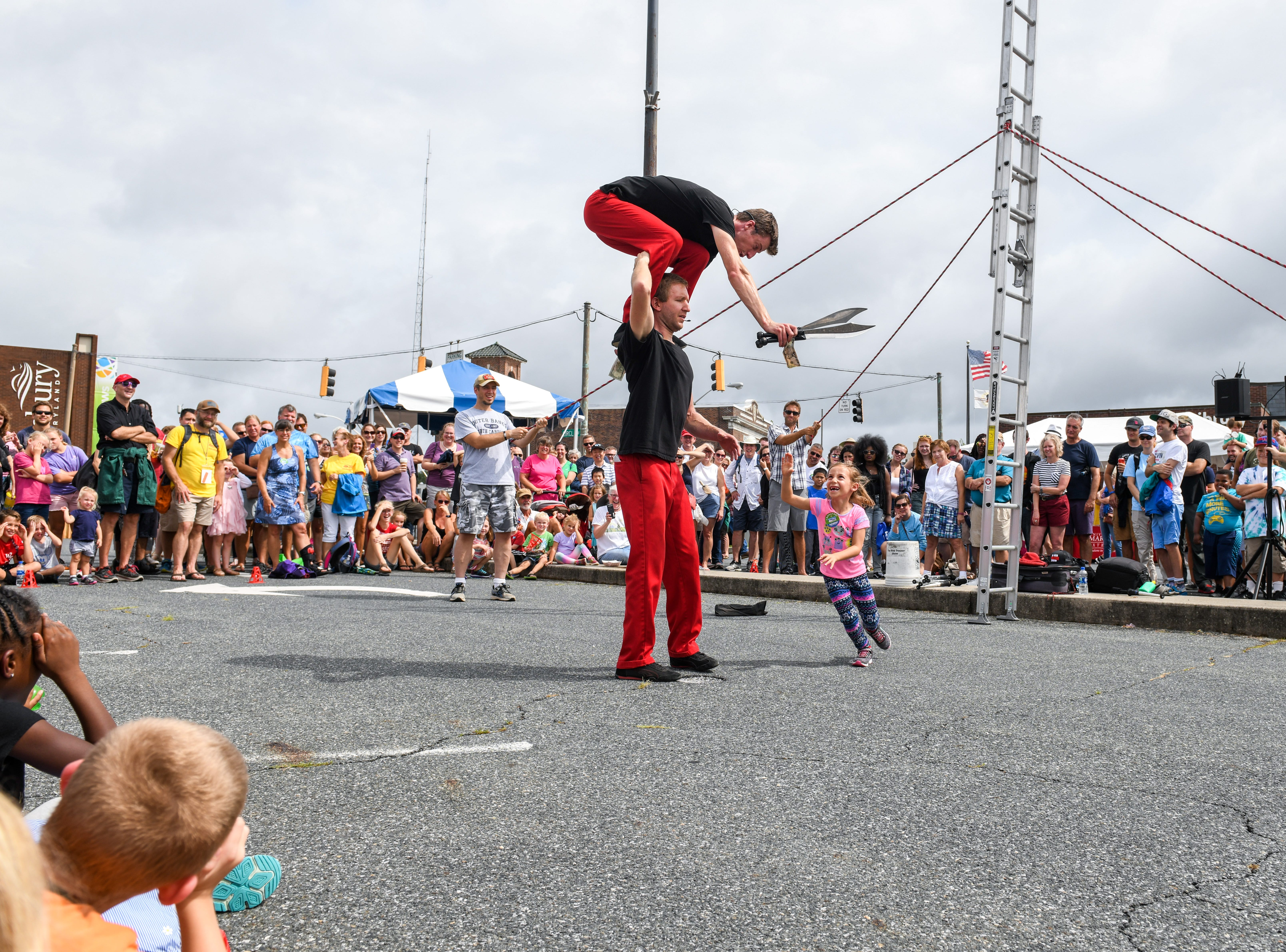 6-year-old Julia Chahalis helps out in the Red Trouser Show performance at the National Folk Festival in Salisbury on Saturday, Sept. 8.