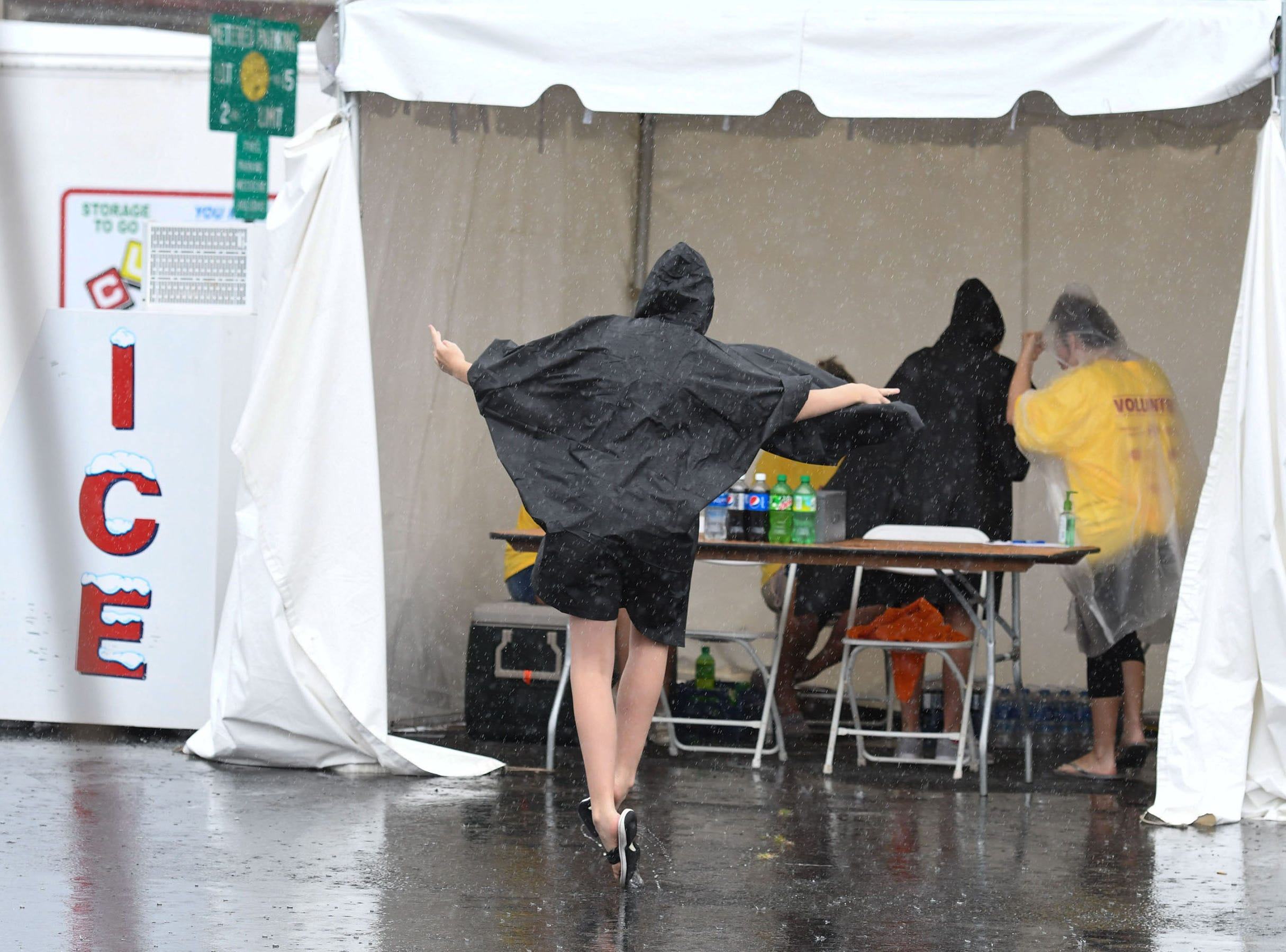 A volunteer takes a moment to practice her ballet in the rain  during the 78th National Folk Festival in Salisbury, Md. on Saturday, Sept. 8, 2018.