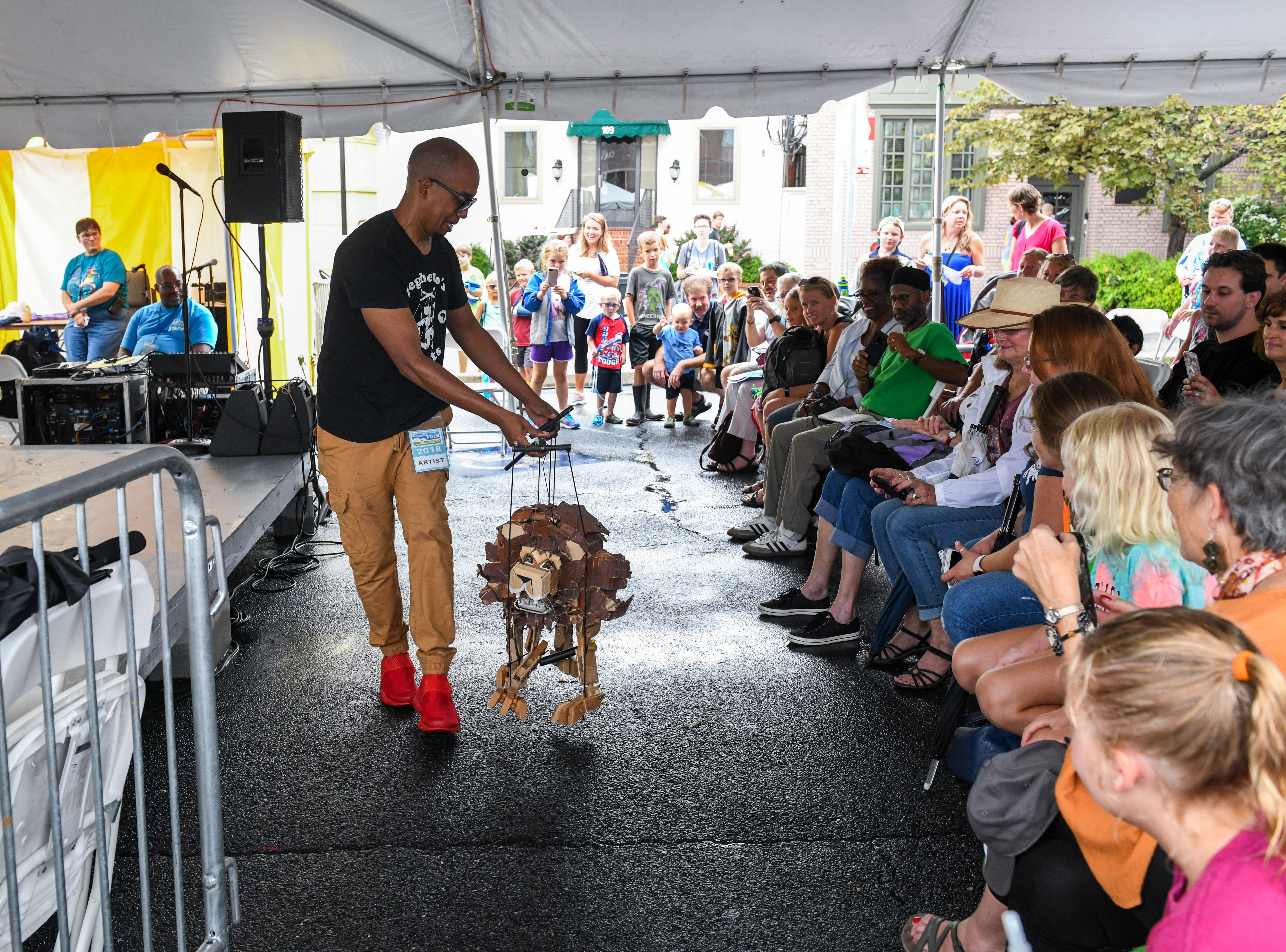 Tarish Papkins of the Jeghetto puppetry group shows off one of their creations to the crowd at the National Folk Festival in Salisbury on Saturday, Sept. 8.