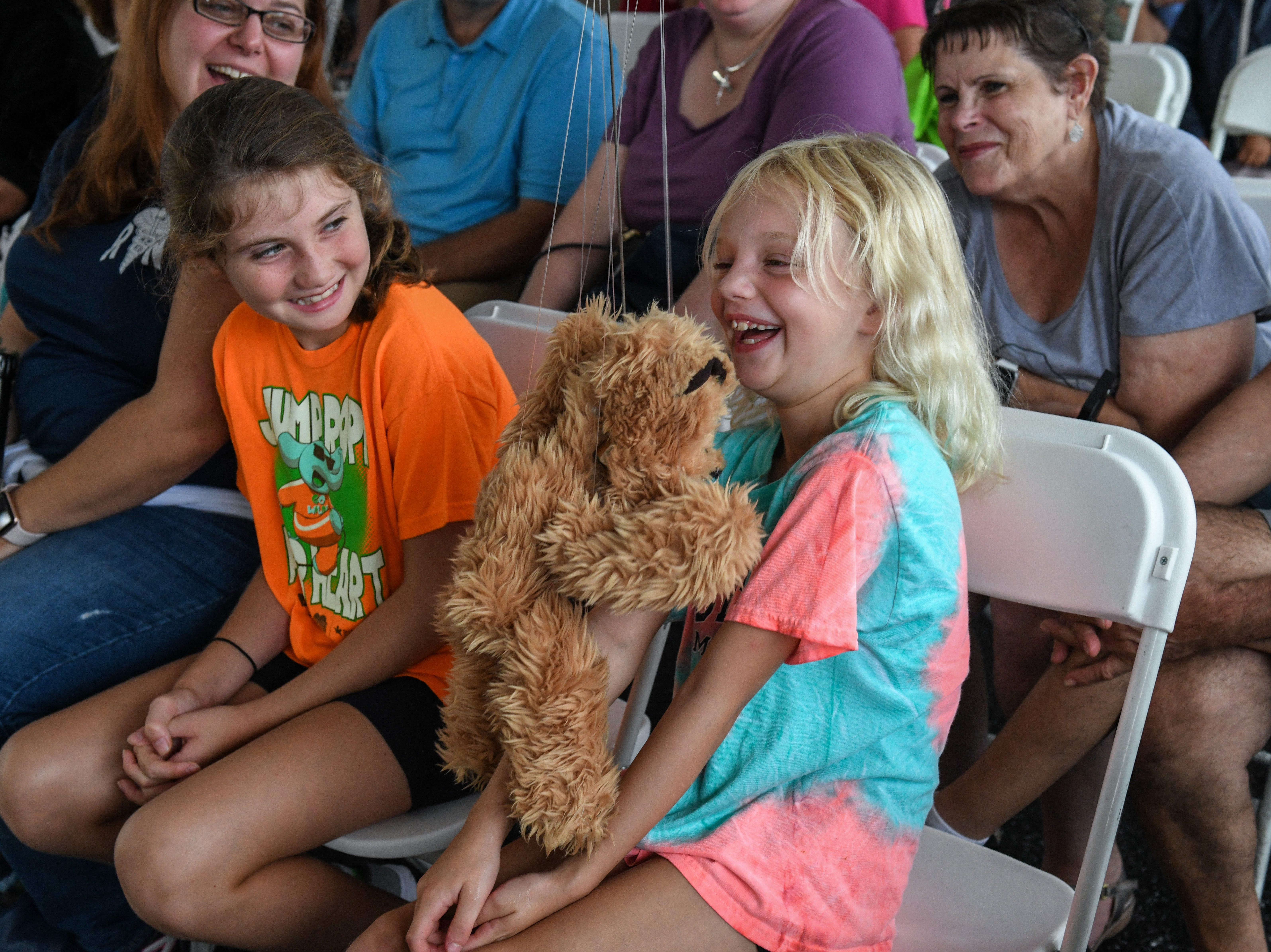 Tarin Papkins of the Jeghetto puppetry group shows a puppet to 7-year-old Audrey Hill at the National Folk Festival in Salisbury on Saturday, Sept. 8.