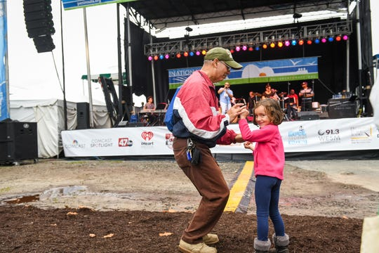 Juan Perez and 6-year-old Mia Paxson dance to the music of Orquesta SCC at the National Folk Festival in Salisbury on Saturday, Sept. 8.