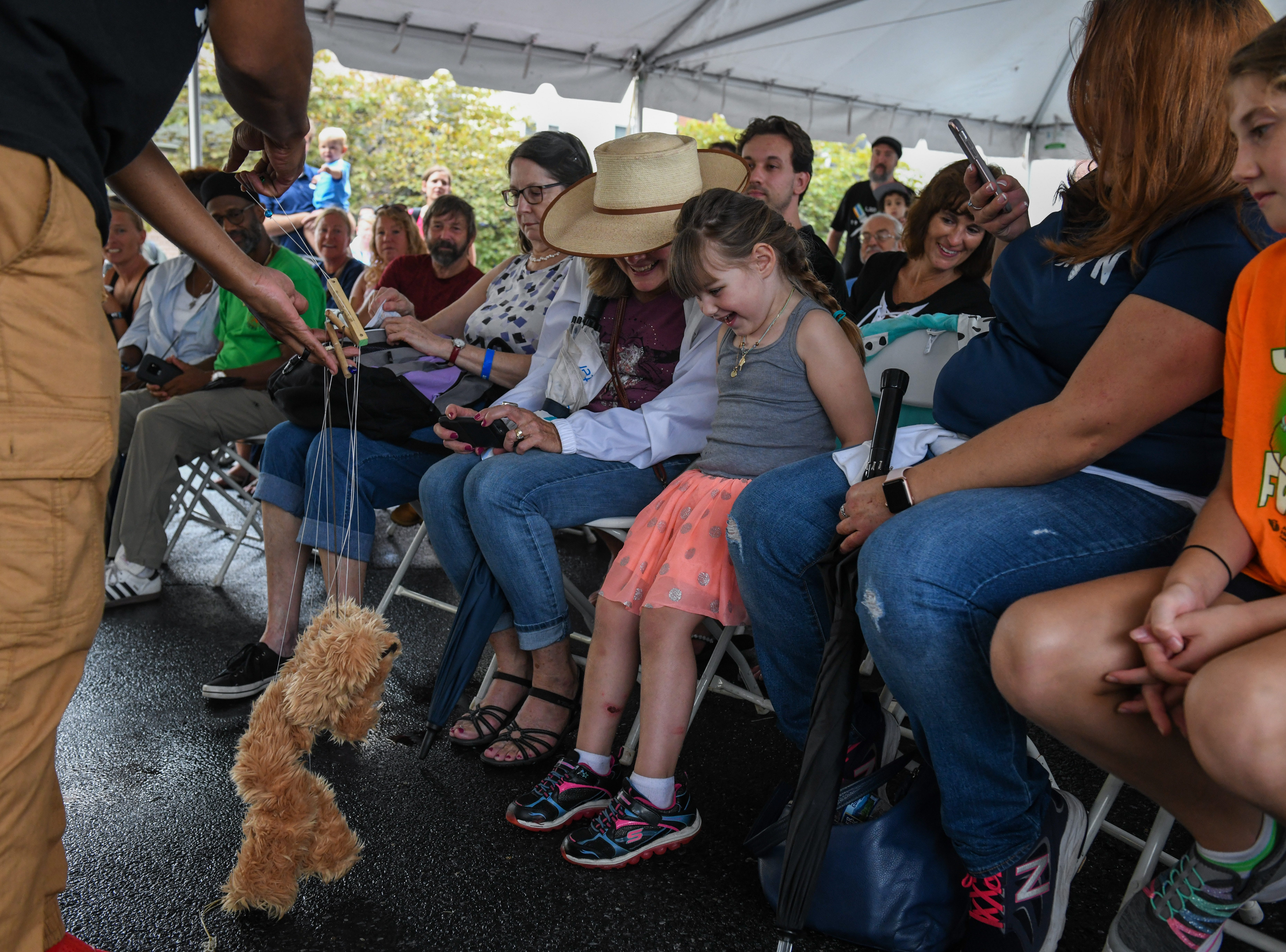 Tarin Papkins of the Jeghetto puppetry group shows a puppet to 5-year-old Lillian Brown at the National Folk Festival in Salisbury on Saturday, Sept. 8.