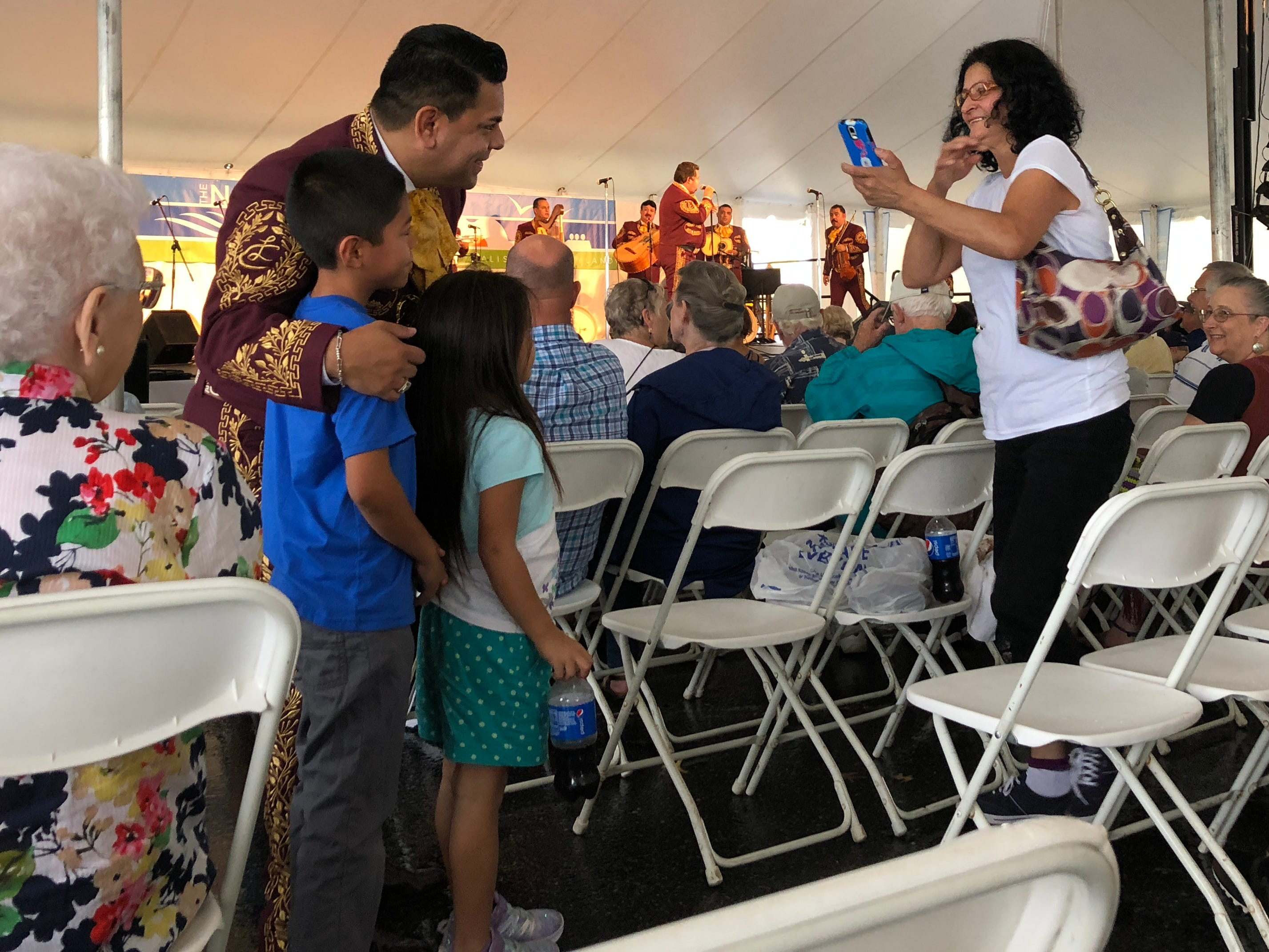 Marta Garcia of El Salvador takes a photo of her children with a Mariachi Los Camperos performer on Saturday, Sept. 8, 2018, at the National Folk Festival in Salisbury, Maryland.