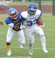 Decatur's Devin Waters runs the ball as Wicomico's Ronnie Stchell tries to take him down during game action Friday at Wicomico High School in Salisbury.