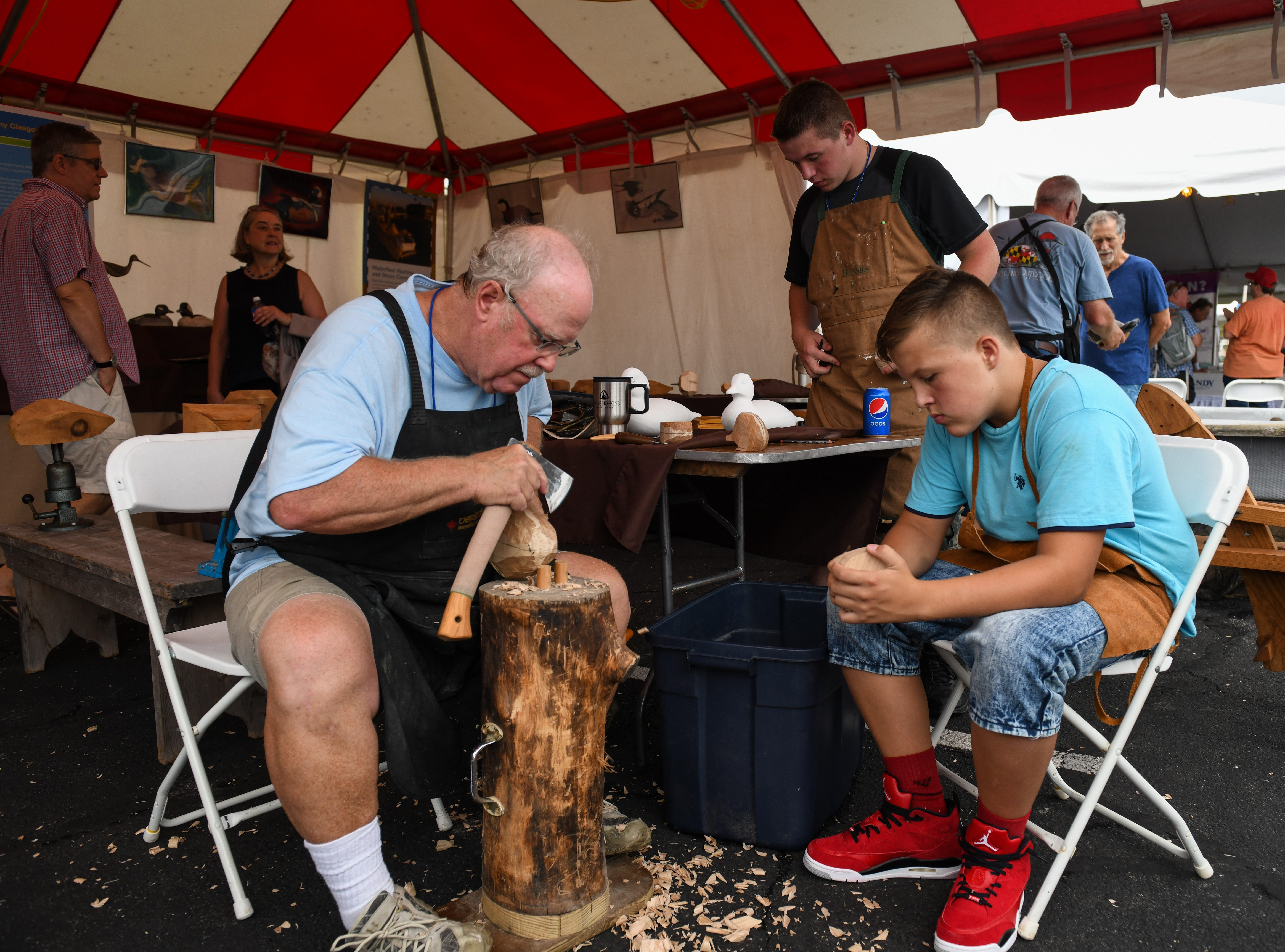 Master carver Rich Smokers and apprentice Wyatt Lowe carve at the National Folk Festival in Salisbury on Saturday, Sept. 8.