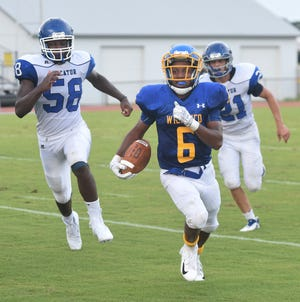 Wi-Hi's Ronnie Satchell breaks away from Decatur's Daletez Smith, left, and Tyler Corrus during game action Friday at Wicomico High School in Salisbury.