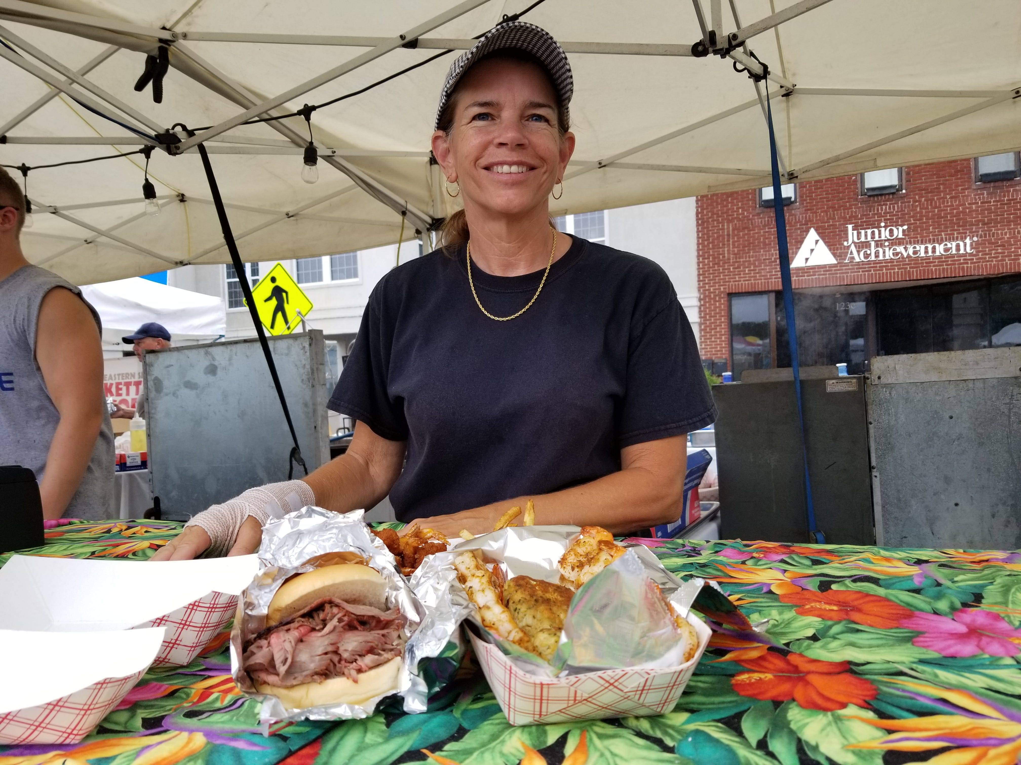 Mollie Failkner of The Milestone in Easton sells crab cakes and other fare near the Henson Stage at the National Folk Festival in Salisbury.