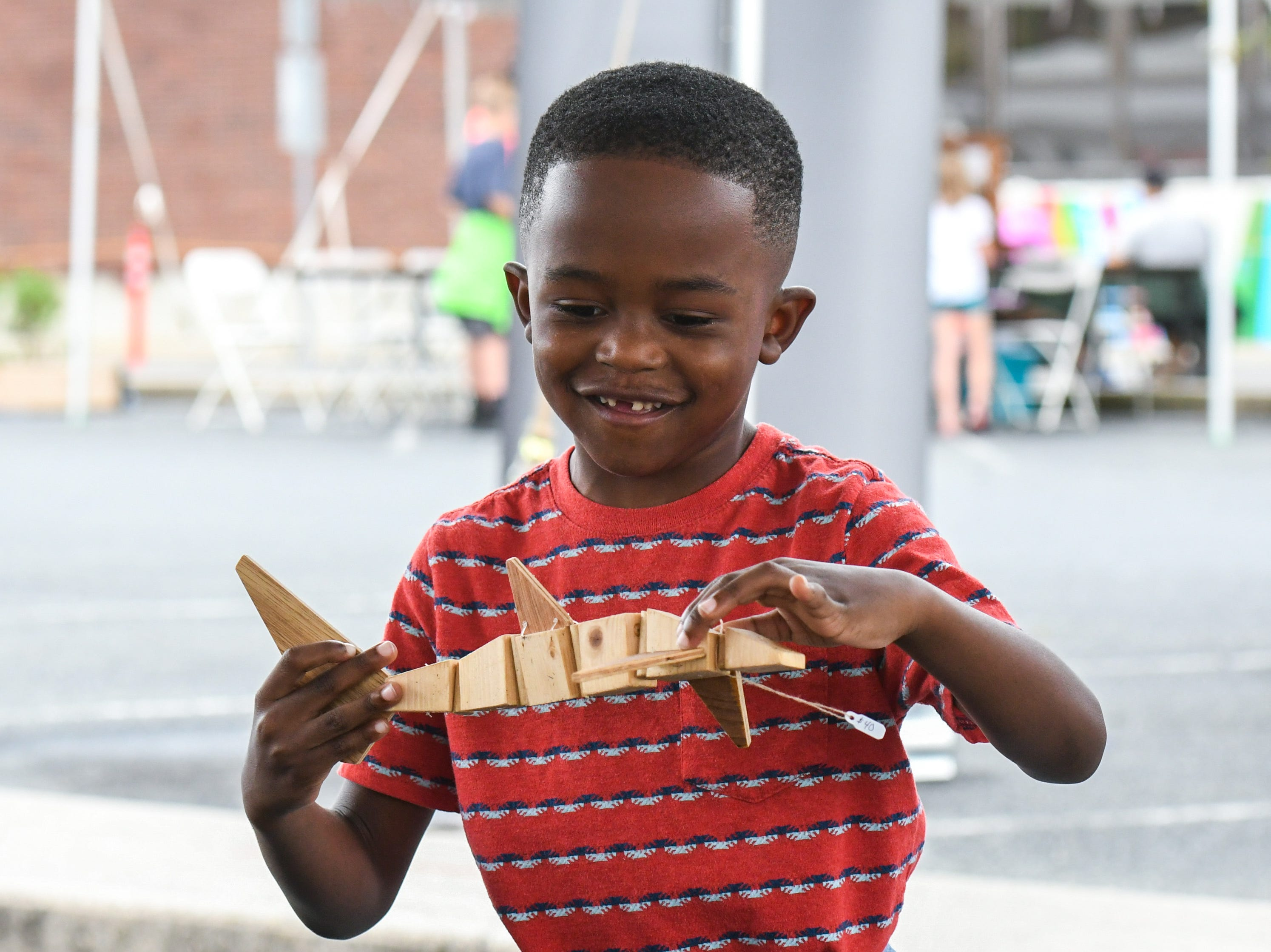 6-year-old Carter McCoy checks out one of the Jeghetto group's puppets at the National Folk Festival in Salisbury on Saturday, Sept. 8.