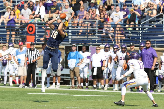 Augustana's WR #18 Sean Engel attempts to catch a pass from QB Kyle Saddler as a defender bares down on him.