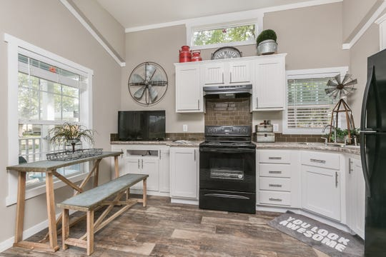 The living area features a kitchen with full-size appliances, a cleverly designed entertainment storage area, dining for two and a comfortable couch.
