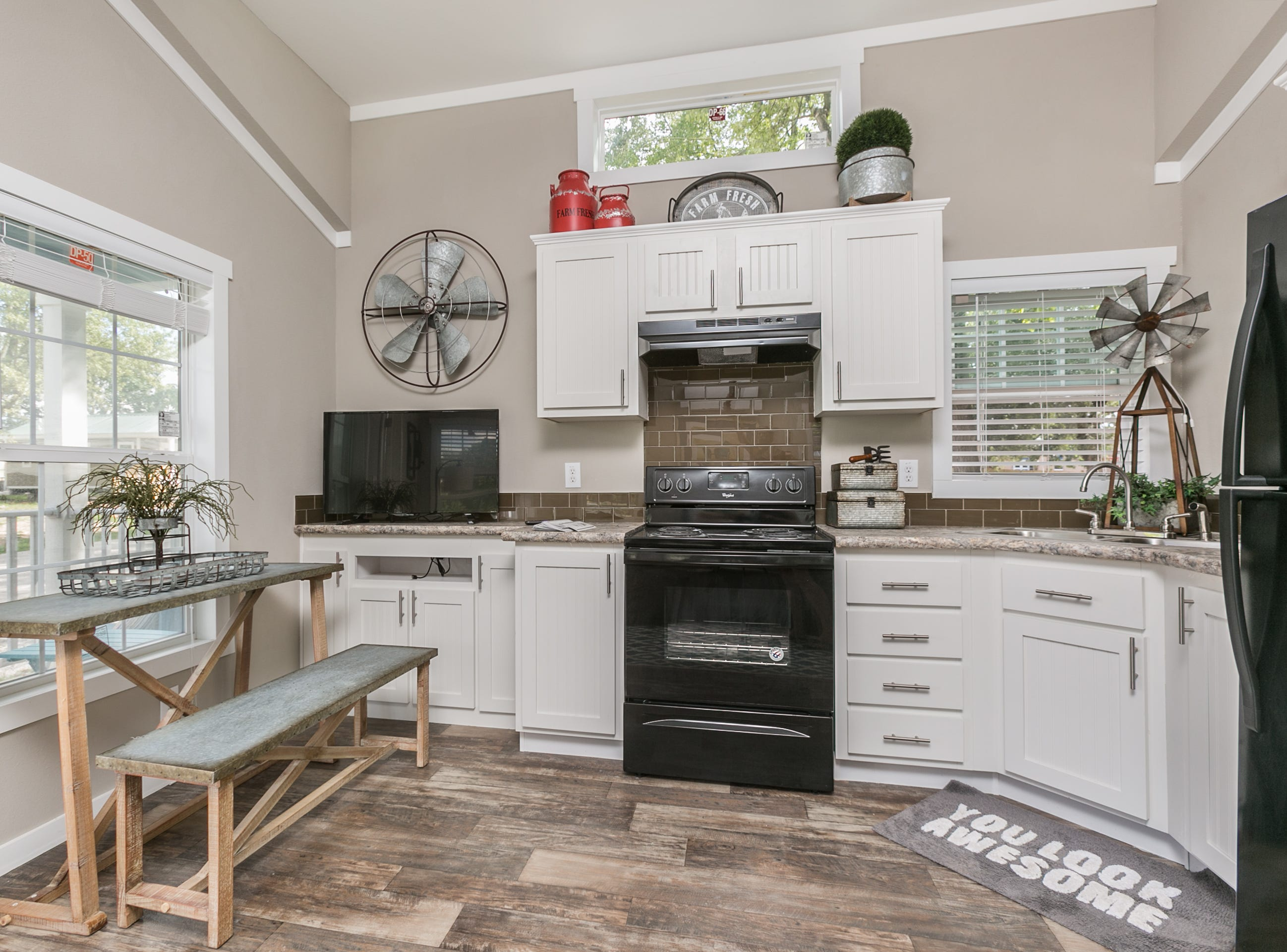 The living area features a kitchen with full-size appliances, a cleverly designed entertainment storage area, dining for two and a comfortable couch. Eden Village home donated by Mike and Mary Walker taken on September 4th, 2018.