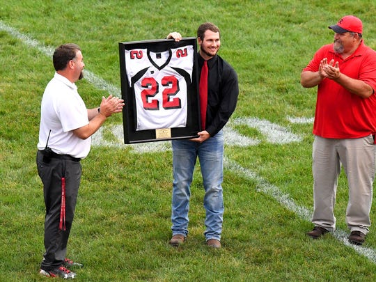 Logan Moore, a 2013 Riverheads graduate holds up the jersey he was presented by school athletic director C.J. Vandevander, left, as the school retired his No. 22 in a ceremony prior to the Gladiators' football game with Stuarts Draft on Friday, Sept. 7, 2018 in Greenville, Va.