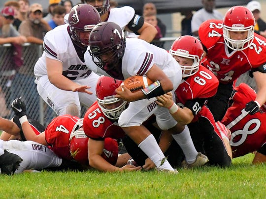 Stuarts Draft's Freddie Watkins is brought down by Riverheads' Davis Cogar and Bryan Hostetler during a football game played in Greenville on Friday, Sept. 7, 2018.