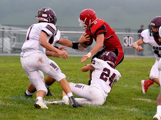 Riverheads' Zac Smiley starts to go down with the ball as Stuarts Draft's Dustyn Fitzgerald and Aaron Nice get in on the tackle during a football game played in Greenville on Friday, Sept. 7, 2018.