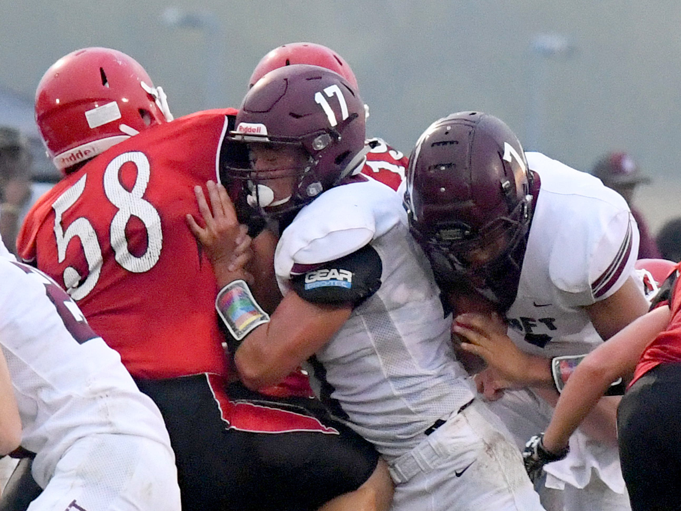 Stuarts Draft's Freddie Watkins (center) has the ball as he tries to squeeze through a hole being opened by teammate Kasey Branch who pushes back Riverheads' Davis Cogar during a football game played in Greenville on Friday, Sept. 7, 2018.