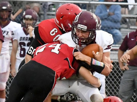 Stuarts Draft's Aaron Nice braces himself with the ball as he is caught between Riverheads' Jaden Phillips and Bryan Hostetler during a football game played in Greenville on Friday, Sept. 7, 2018.