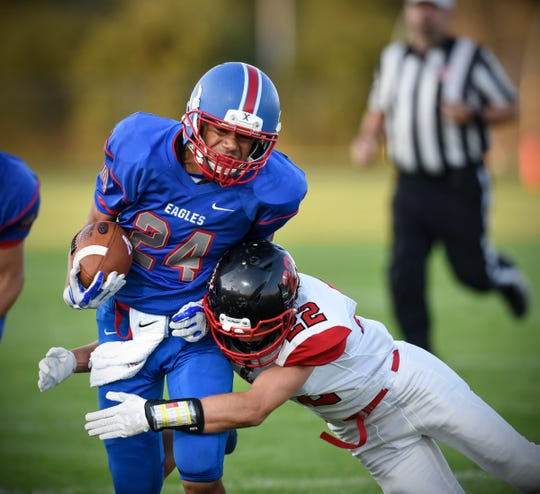 Apollo's Lukas Theisen tries to avoid a tackle by Christopher Clark of ROCORI during the Friday, Sept. 7, game at Apollo High School in St. Cloud.