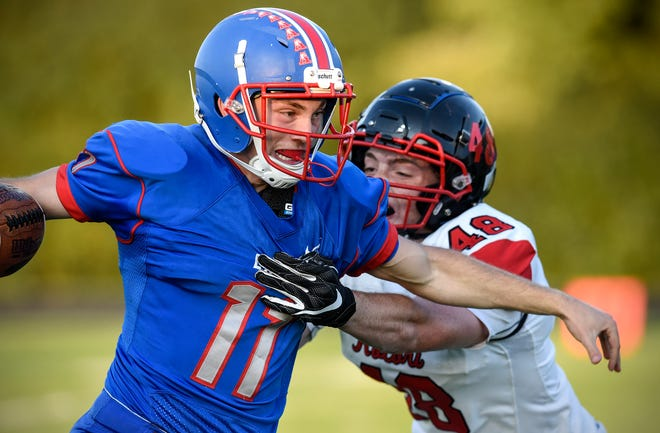 Apollo quarterback Neal Benson tries to avoid a tackle by ROCORI's Nathaniel Venable during the Friday, Sept. 7, game at Apollo High School in St. Cloud.