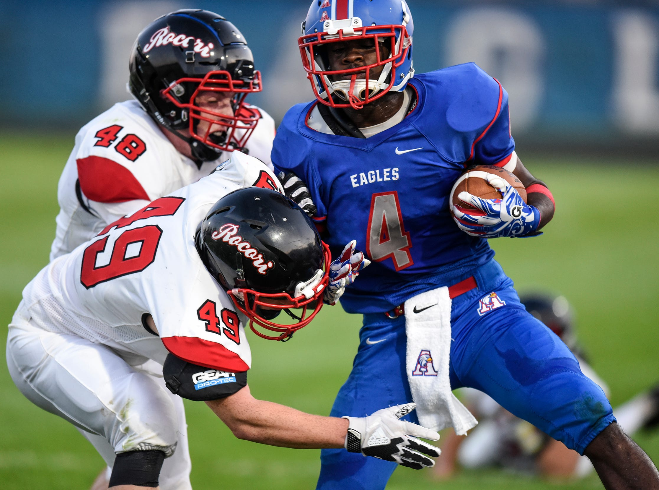 Nathaniel Venable (48) and Alex Wenner (49) of ROCORI team up to tackle Apollo's Clifton Patterson during the Friday, Sept. 7, game at Apollo High School in St. Cloud.