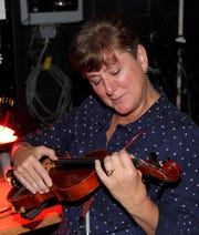 Karen Wiggins trying her hand at the violin during intermission of an orchestra concert at the Vero Beach High School Performing Arts Center.