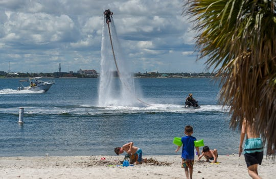 """Hydro Militia team member Scott Geltman of Jupiter (center left) practices water jet pack maneuvers Saturday, Sep. 8, 2018, as his teammate, Mike Traster of Sebastian, navigates the connected jet ski at Jaycee Park in Fort Pierce. The city of Fort Pierce is considering a new ordinance that would prohibit kayaking, jet skiing, people bringing barbecue grills, having a bounce house, playing music at the park that can be heard more than 100 feet away, and using the restroom to shower and bathe unless shower facilities are specifically provided for public use. Also, skating and skateboarding would only be allowed in designated areas. """"I think it would kill a lot of the touristic things we do. It'd be a real detriment to our lifestyle here,"""" said Traster of the potential ordinance. To see more photos, go to TCPalm.com."""