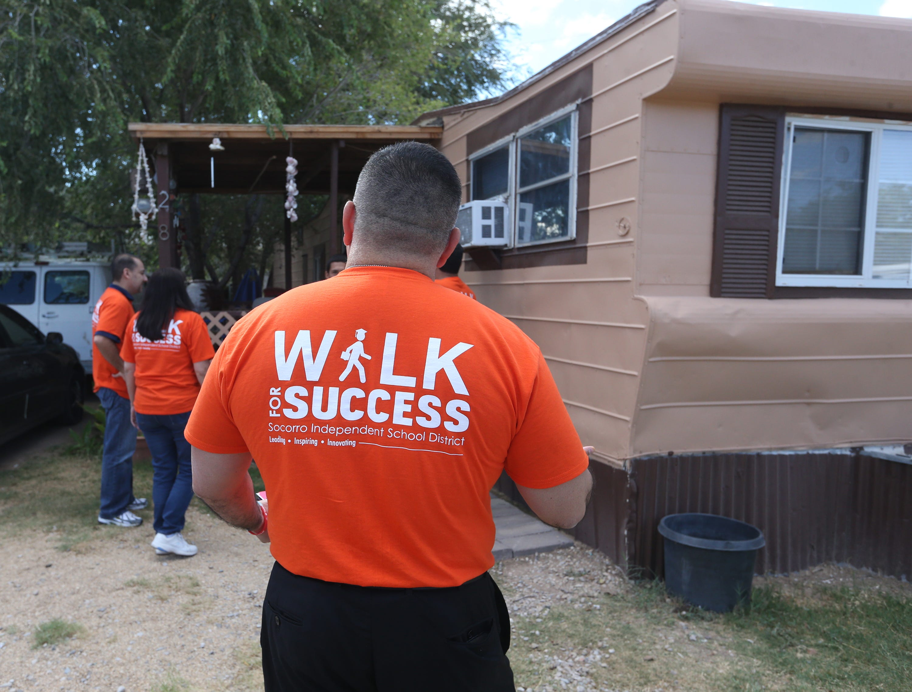 Josh Tovar, principal at Socorro High School walks to a home to meet with a young man who is currently not enrolled in school Saturday. The team convinced the young man, who left school after his junior year, to meet with Tovar Monday morning to discuss his return to school.