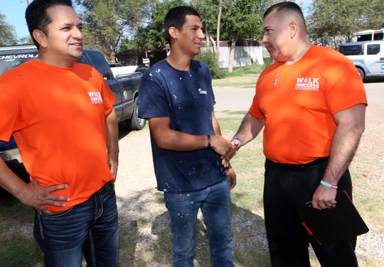 "Socorro High School Principal Federico ""Josh"" Tovar, right, and Socorro Independent School District Superintendent Jose Espinoza, left, meet with Israel Rubio, 18, who left high school after his junior year, outside his Socorro home in 2018. The team convinced him to meet with Tovar about returning."