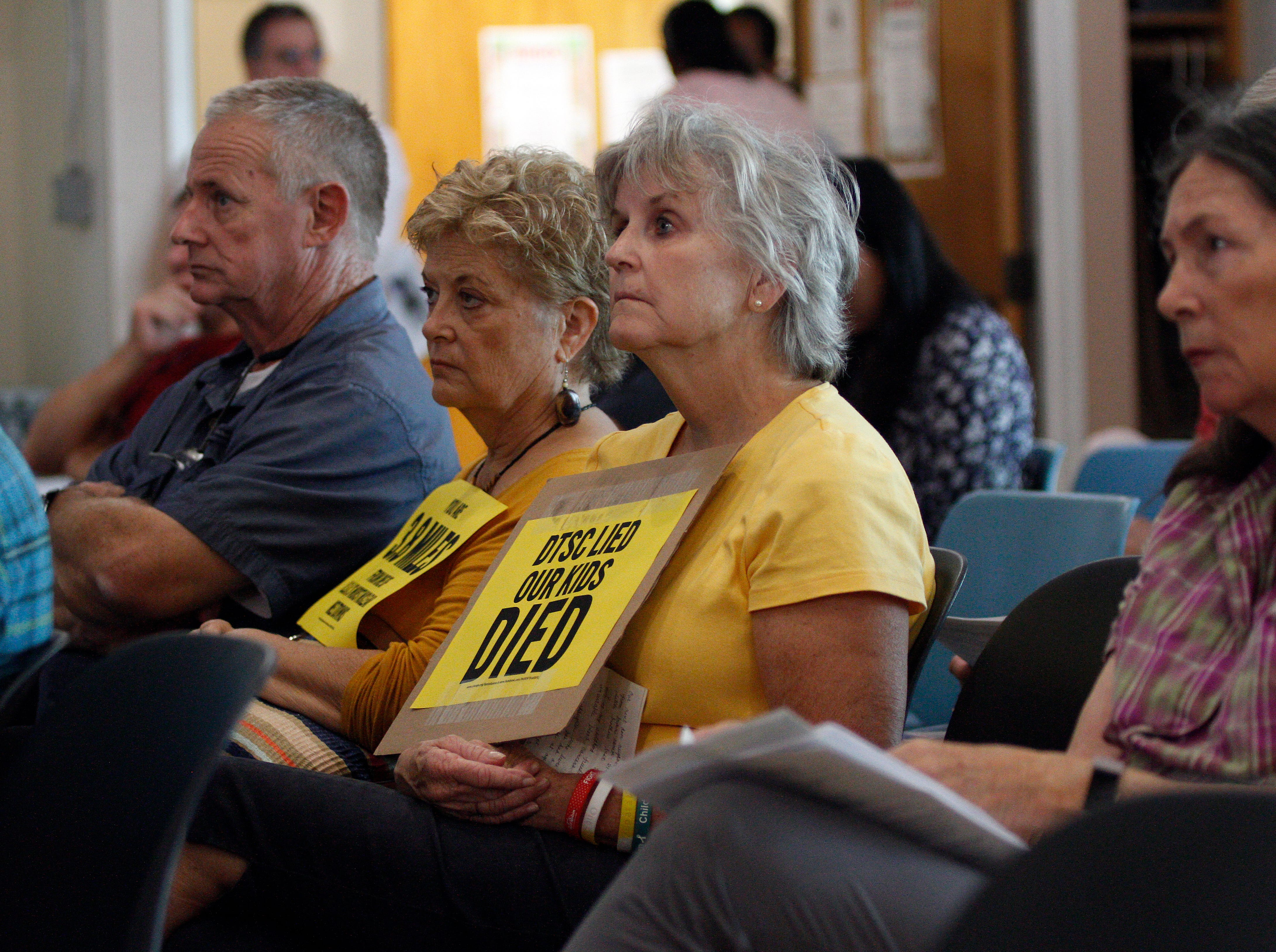 Deva Andrews, left, and Karin Carlson hold signs to protest the California Department of Toxic Substances Control's handling of the proposed cleanup of the Santa Susana Field Lab during a public hearing Saturday at the Simi Valley Senior Center.