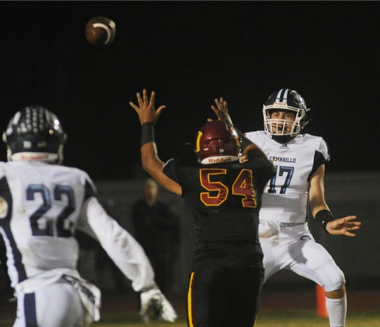 Camarillo High quarterback James McNamara lofts a pass over Oxnard's Gilbert DeLaTorre as Carson Anderson waits to make the catch during Friday night's game.