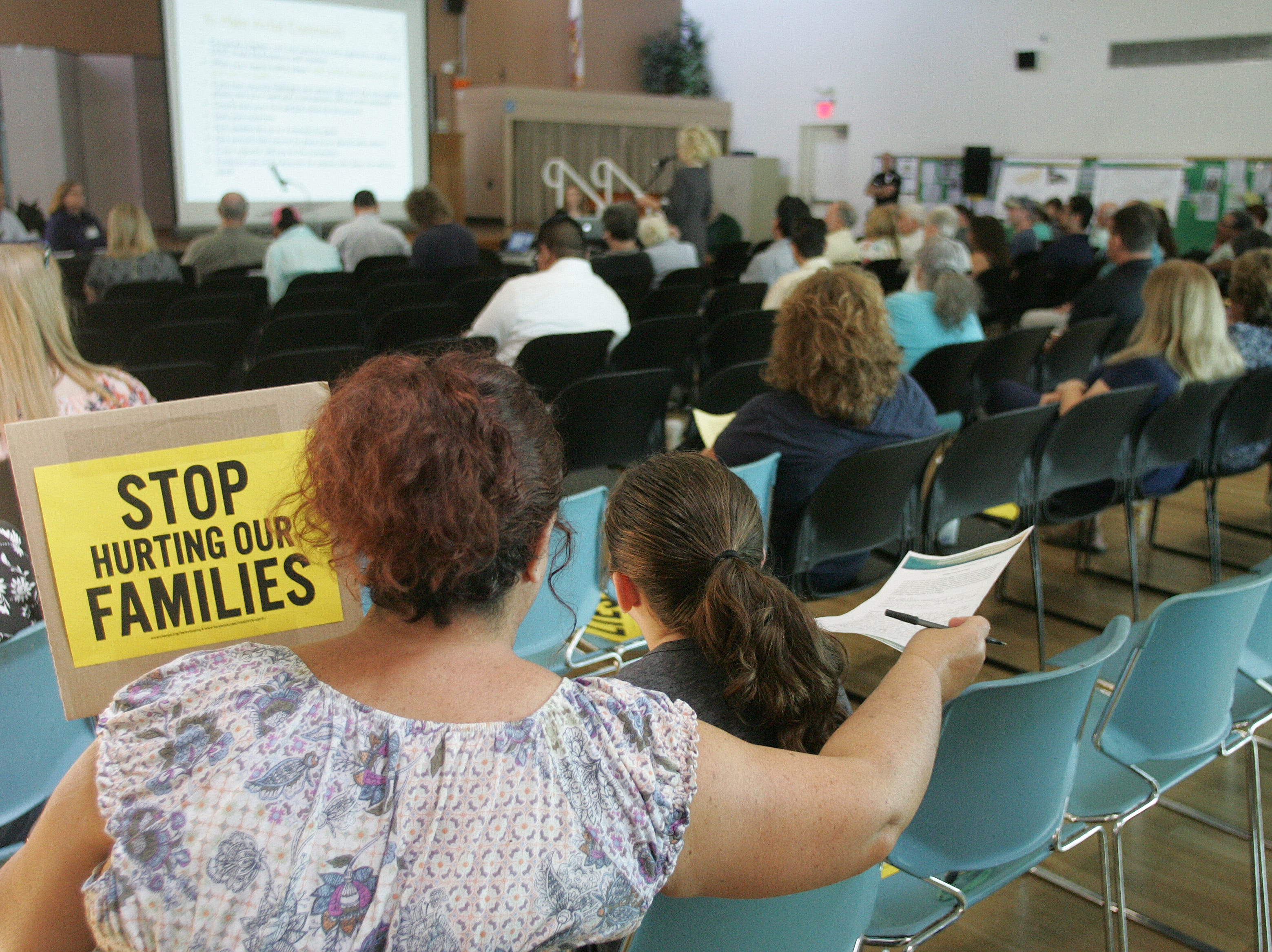 Lisa Geer and her daughter Natalie listen to the speakers while holding signs to protest the California Department of Toxic Substances Control's handling of the proposed cleanup of the Santa Susana Field Lab during a public hearing Saturday at the Simi Valley Senior Center.