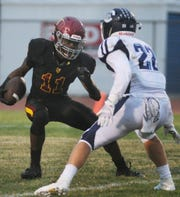 Oxnard High's Xavier Harris, left, tries to slip past Camarillo's Carson Anderson during Friday night's game at Oxnard. Camarillo remained unbeaten with a 35-19 victory.