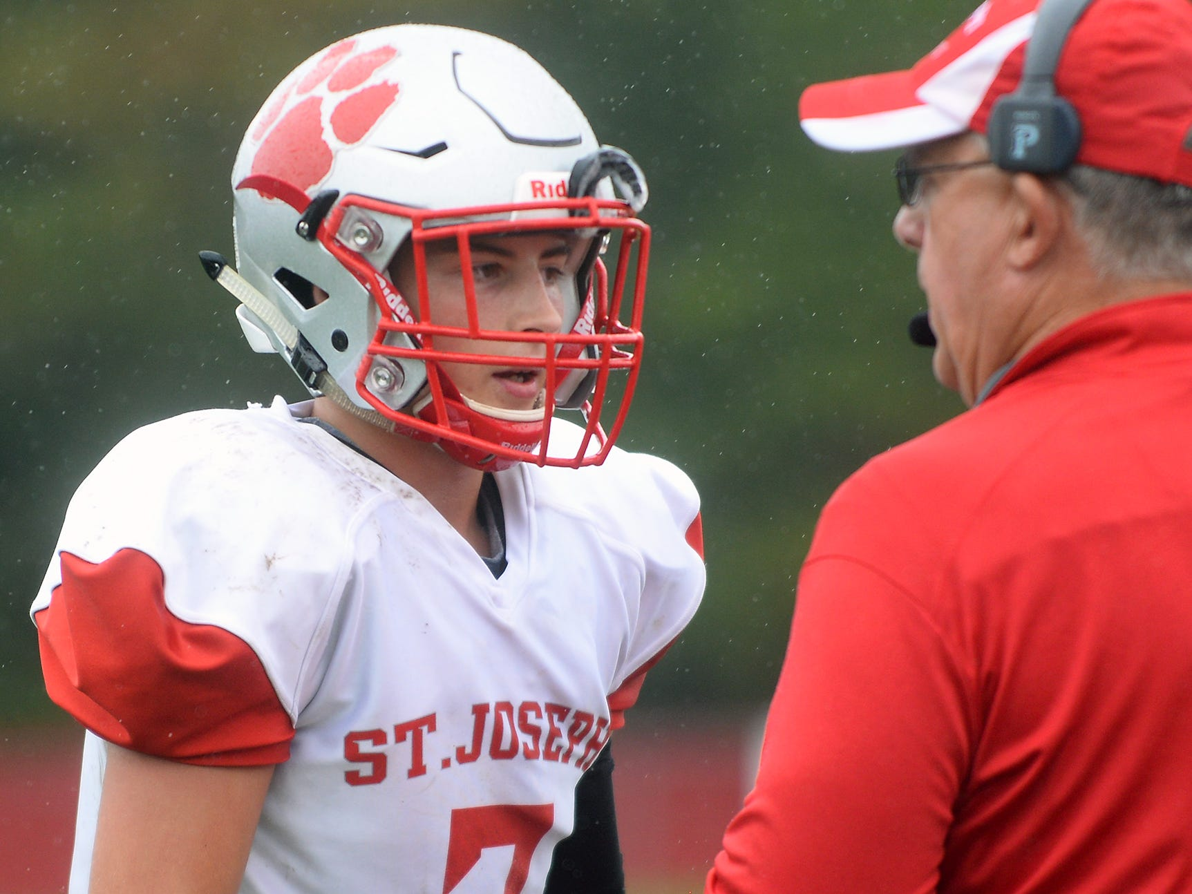 St. Joeseph QB Jayden Shertel (7) talks to coach Rob Neuber during a game against Millville. The Wildcats rolled past the Thunderbolts 34-6 in Hammonton on Saturday, September 8.