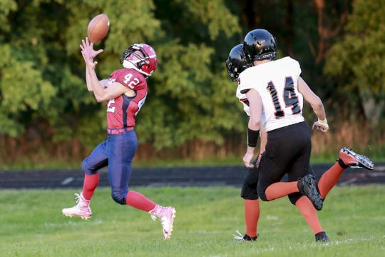 Spencer-Columbus' running back Hayden Bauman pulls in a touchdown pass during the first quarter while Stanley-Boyd's Ben Milas (82), and LJ Schmelzer (14) trail on the play during Friday's Cloverbelt Conference game in Spencer.