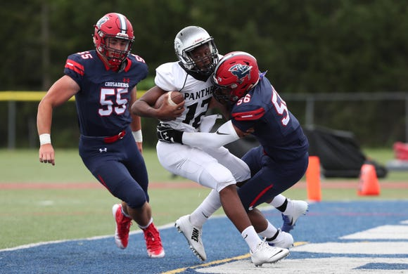 Central Dauphin East quarterback Jeremiah Green (12) gets sacked in the end zone by Stepinac's Kevin Gray (55) and Dougie Simmons (56) for a first half safety during football action at Archbishop Stepinac High School in White Plains Sept. 8, 2018. Stepinac won the game 32-14.