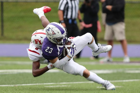 John Jay's James Machado (23) gets tackled by Fox Lane's Sean Simmons (8) after a first half catch during football action at John Jay High School n Cross River Sept. 7, 2018.