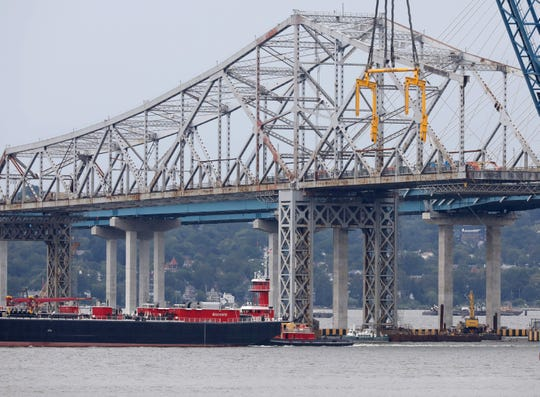 Tugboats push barges along the Hudson River, beneath the old Tappan Zee Bridge, Sept. 8, 2018.