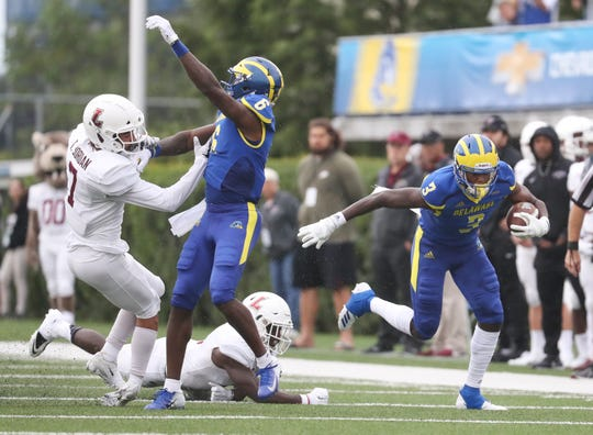Delaware receiver Joe Walker (right) gets past one Lafayette defender and a block from teammate Jamie Jarmon on another as he gains ground after a catch in the first quarter at Delaware Stadium.