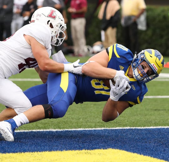 Delaware's Bryce De Maille falls into the end zone for a touchdown reception as Lafayette's Trent Crossan defends in vain in the first quarter at Delaware Stadium.