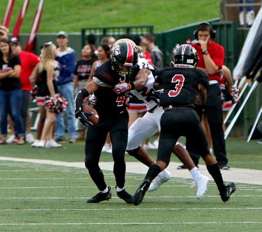 Wichita Falls High's Isaiah Johnson (4) tries to break away from Saginaw's Sean Verdun (23) on Friday, Sept. 7, 2018, at Memorial Stadium.