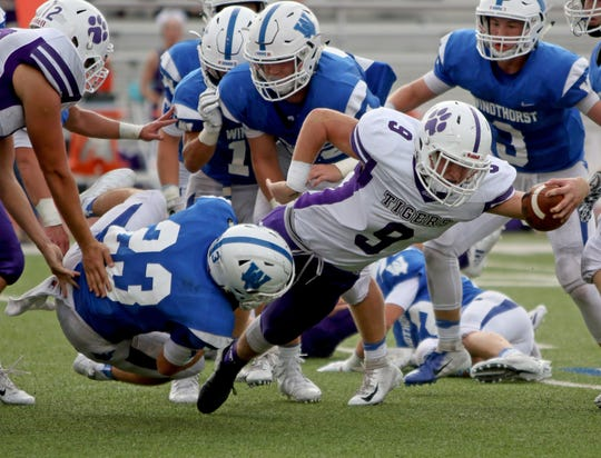 Jacksboro's Brayden Pewitt reaches for an extra yard as he is tackled by Windthorst's Nathan Bales Friday, Sept. 7,  2018, in Windthorst.