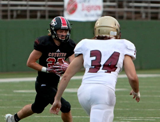 Wichita Falls High's Dayton Romines (left) looks for a running lane to get past Saginaw's Andy Delgadillo (34) on Friday, Sept. 7, 2018, at Memorial Stadium.