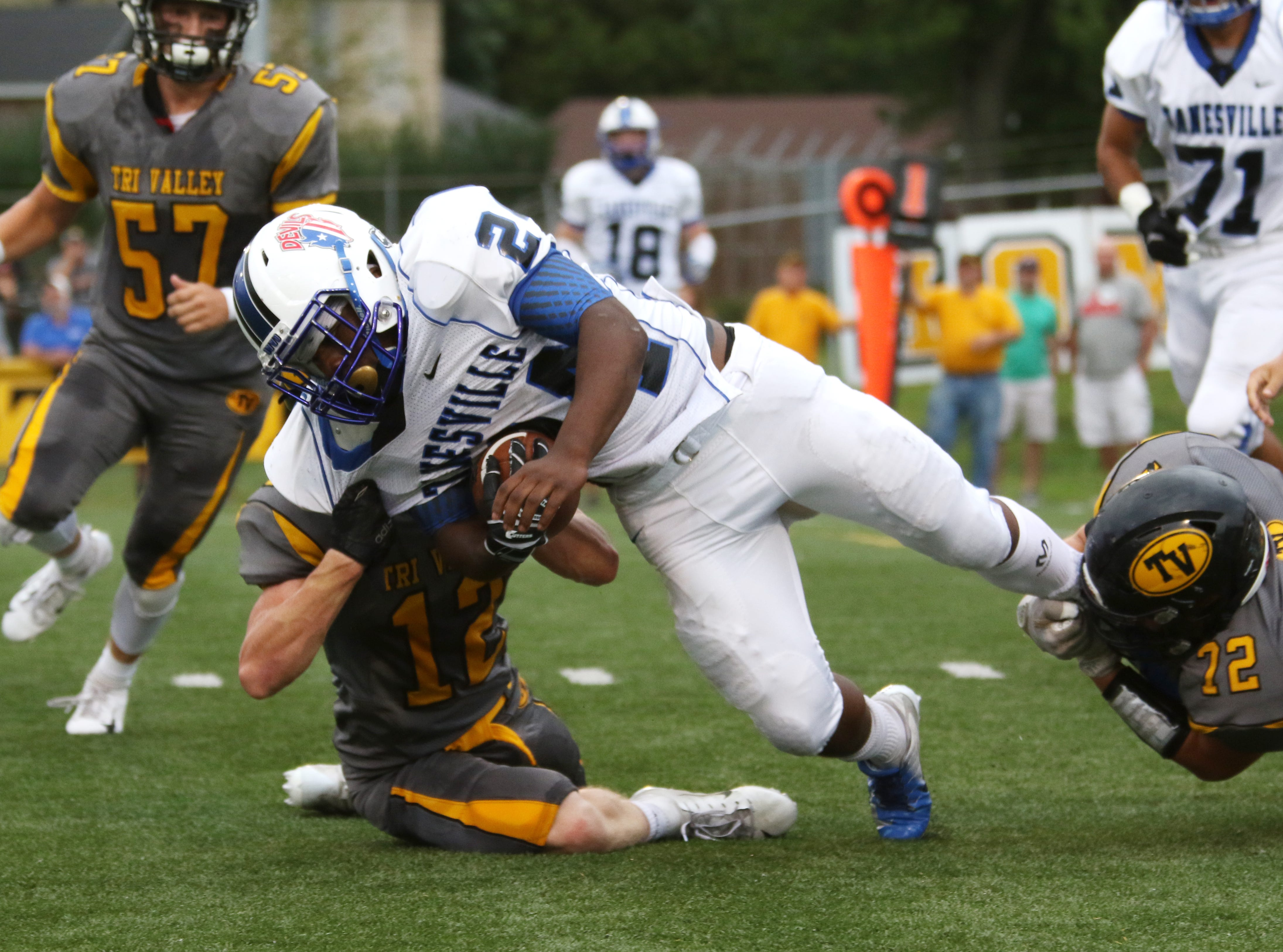 Tri-Valley's Graham Cameron (12) and Seth Tyson tackle Zanesville's Jalen Haley.